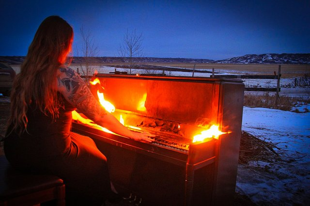 pcredit Andrea Lawrence  - pianist playing in February while keys burn.jpg